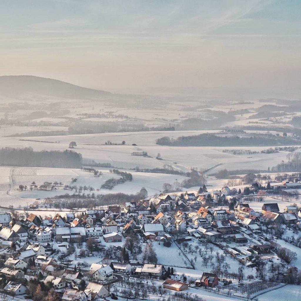 Blick auf das verschneite Schlaifhausen. Hätte das Foto Ton, so würde man eine Blaskapelle durch das Dorf ziehen hören. #forchheimshots #igersforchheim #winterzauber #winterwonderland #ig_franken #igersfranconia #igersfranken #schlaifhausen #walberla #german_landscape